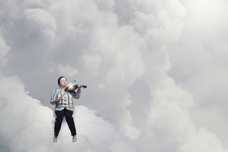 stout: Middle aged stout woman on cloud playing violin Stock Photo