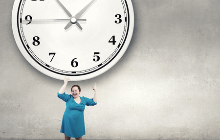 stout: Middle aged stout woman in blue dress pointing at clock Foto de archivo
