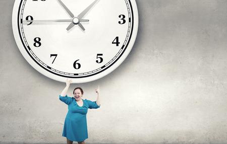 stout: robusta mujer de mediana edad en azul vestido apuntando a un reloj