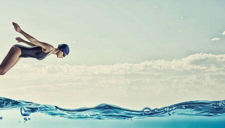 competencia: Joven nadador de competición mujer en pose de partida