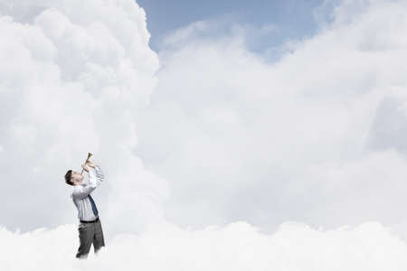 blow: Young businessman on cloud in sky playing pipe