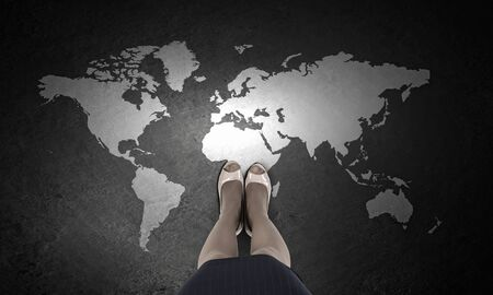 top of the world: Top view of businesswoman feet and world map on floor