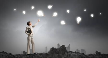 mente humana: Adult woman in suit with old book in hand pointing at light bulb