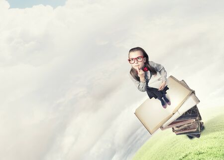young schoolgirl: Wideangle picture of funny schoolgirl with paper plane in hand Stock Photo