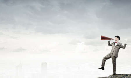 emotionally: Young businessman on rock top screaming emotionally in paper trumpet Stock Photo