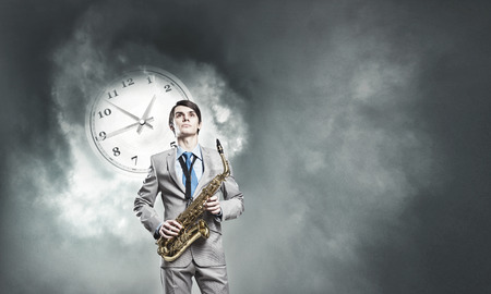 jazz time: Young man in suit with saxophone in hands Stock Photo