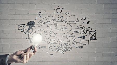 illuminating: Glowing light bulb illuminating business sketches on wall