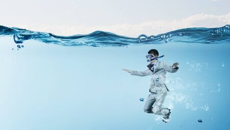 business challenge: Young businessman in suit and diving mask jumping in water