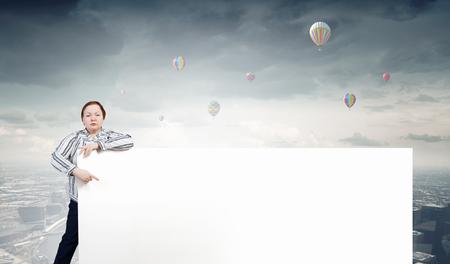 stout: Mujer Stout de mediana edad apuntando a la bandera blanca en blanco