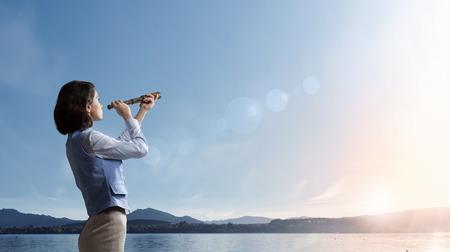horizonte: Empresaria joven que mira en catalejo en la salida del sol en el horizonte