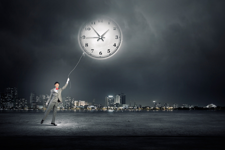 back in time: Young businessman trying to turn back time by pulling clock with rope Stock Photo