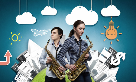 saxophones: Duet of young man and woman musicians playing saxophones