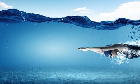 Nadador joven mujer en la gorra y gafas bajo el agua