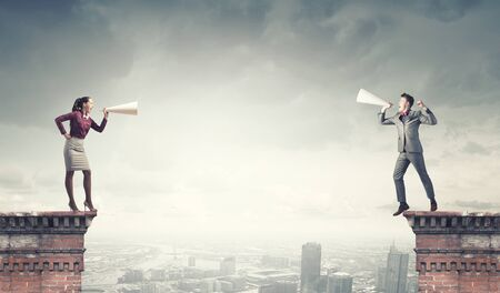 amplify: Young businessman and businesswoman on building top screaming on each other in paper trumpets