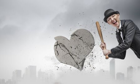 heartbreaker: Young emotional woman in suit and hat with baseball bat