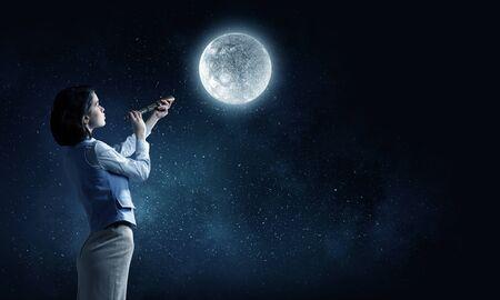 Empresaria joven que mira en catalejo en luna llena en el cielo