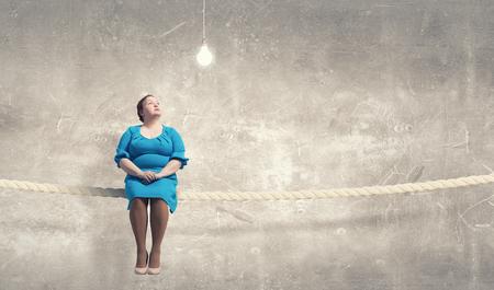 cerveza negra: robusta mujer de mediana edad en el vestido azul que se sienta en cuerda