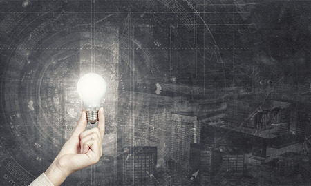electric bulb: Human hand holding a shining electric bulb on digital background