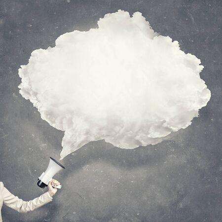 megafono: mano que sostiene el megáfono y el habla nube blanca en blanco Foto de archivo
