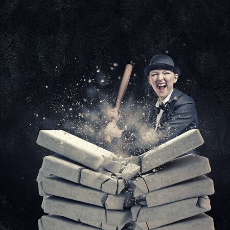 violence in sports: Young emotional woman breaking bricks with baseball bat Stock Photo