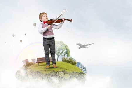 fiddles: Adorable boy wearing red bowtie and playing violin Stock Photo
