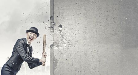 baseball bat: Young pretty woman in suit and hat crashing wall with baseball bat