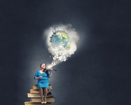 stout: robusta mujer de mediana edad en el vestido azul que se sienta en los libros y que toca el violín. Foto de archivo