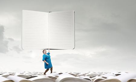 stout: Mujer robusta de mediana edad en el vestido azul que sostiene gran bloc de notas Foto de archivo