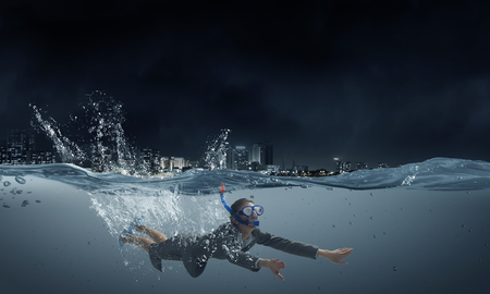 businesswoman suit: Young businesswoman in suit and diving mask swimming under water