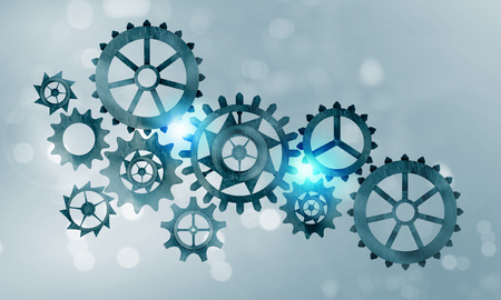 engranajes: Mecanismo de engranajes de metal y ruedas dentadas sobre fondo azul Foto de archivo