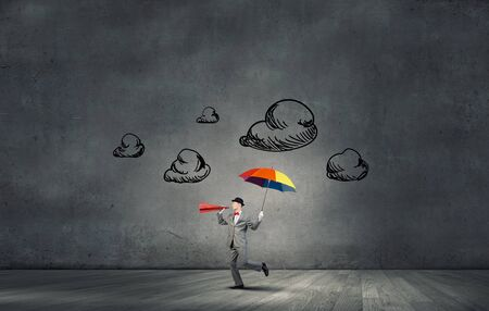 amplify: Young businessman with colorful umbrella screaming emotionally in paper trumpet