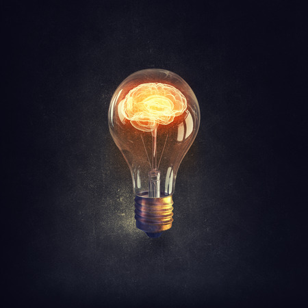 Human brain glowing inside of light bulb on dark background Stock Photo