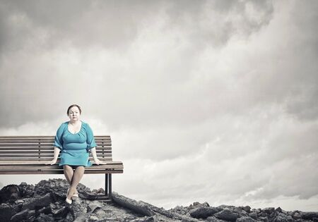 stout: Middle aged stout woman in blue dress sitting on bench Stock Photo