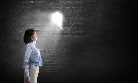 blinded: Young businesswoman blinded with light going from bulb Stock Photo