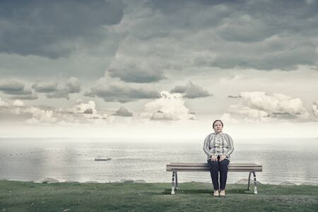 stout: Mujer robusta de mediana edad sentado en el banco