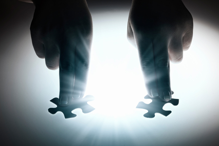 business strategy: Hand connecting two jigsaw glowing puzzle pieces Stock Photo