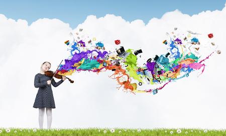 바이올린과 다채로운 밝아진 귀여운 아이 소녀가 밖으로 날기
