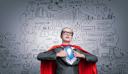 powerful creativity: Businesswoman wearing red cape and opening her shirt like superhero