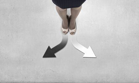 flecha direccion: Top view of businesswoman feet standing at crossroads Foto de archivo