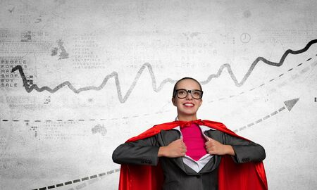 moneymaking: Young businesswoman in red cape acting like super hero