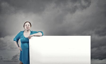 oversize: Confident woman of middle age with blank white banner