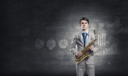 playing the market: Young businessman with saxophone in hands and diagrams at background Stock Photo