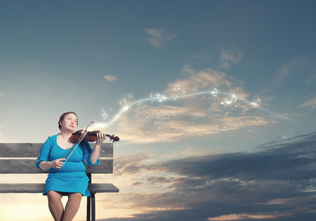 cerveza negra: Mujer robusta de mediana edad en el vestido azul sentada en el banco y que toca el violín Foto de archivo