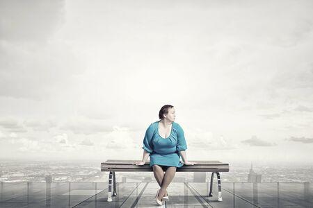cerveza negra: Mujer robusta de mediana edad en el vestido azul sentada en el banco