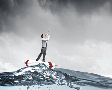 insurance concepts: Young businessman on floating in water buoy playing pipe
