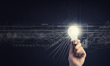 Menselijke hand houden lichtend elektrische lamp en infographs op muur Stockfoto