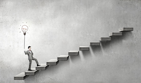 Young businessman climbs ladder of success with lightbulb balloon in hand Standard-Bild