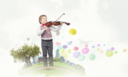 fiddlestick: Adorable boy wearing red bowtie and playing violin Stock Photo