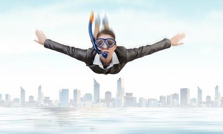 Junge Geschäftsfrau in der Klage und Tauchmaskenfliegen im Himmel