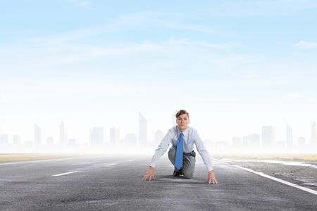 starting position: Young determined businessman in starting position ready to compete
